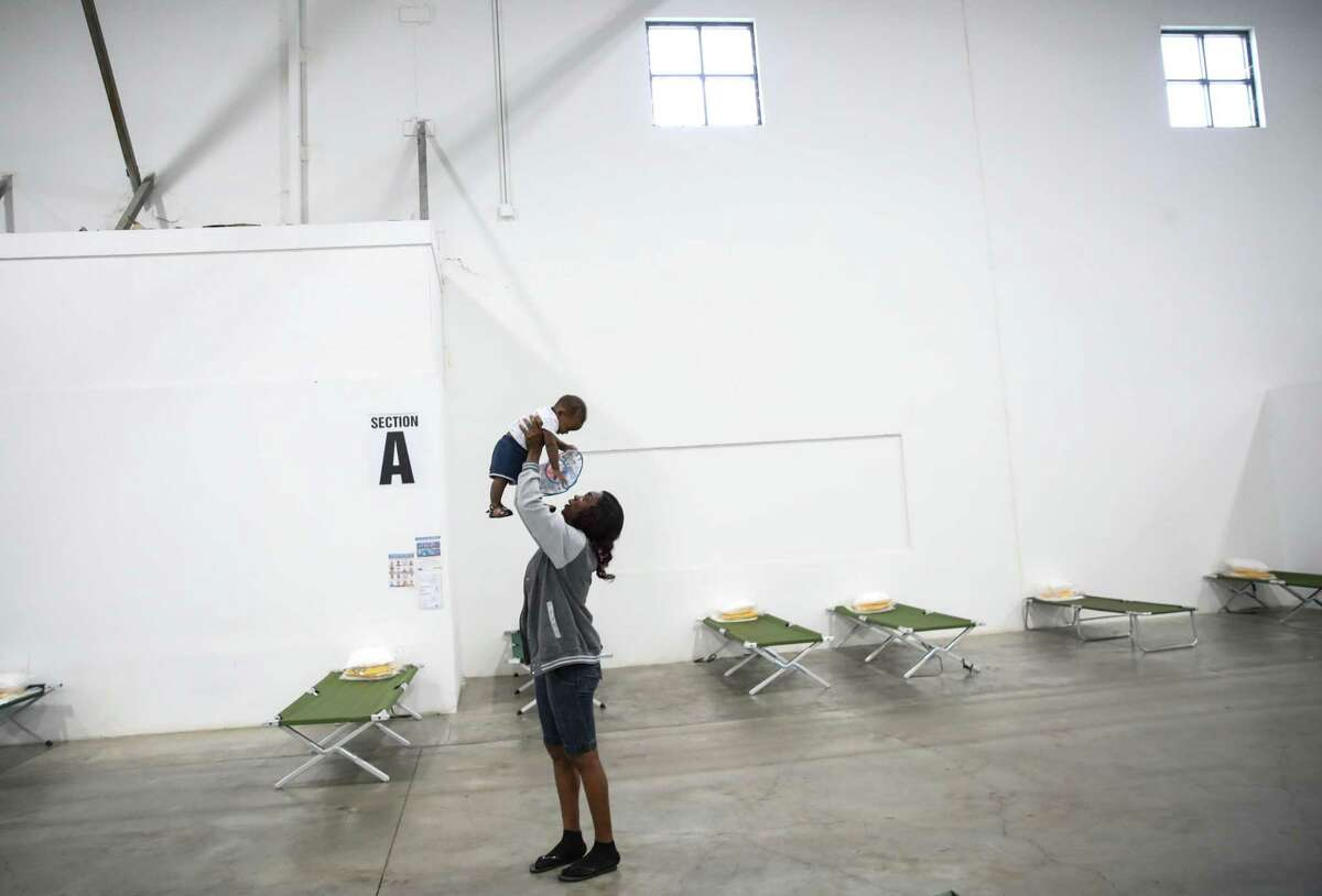 Vallerie Lamour, a Haitian migrant, plays with Jayden Metayer, the child of a woman she met while crossing the Rio Grande near Del Rio, while the mother speaks with a reporter Saturday, June 5, 2021, at a shelter in Houston.