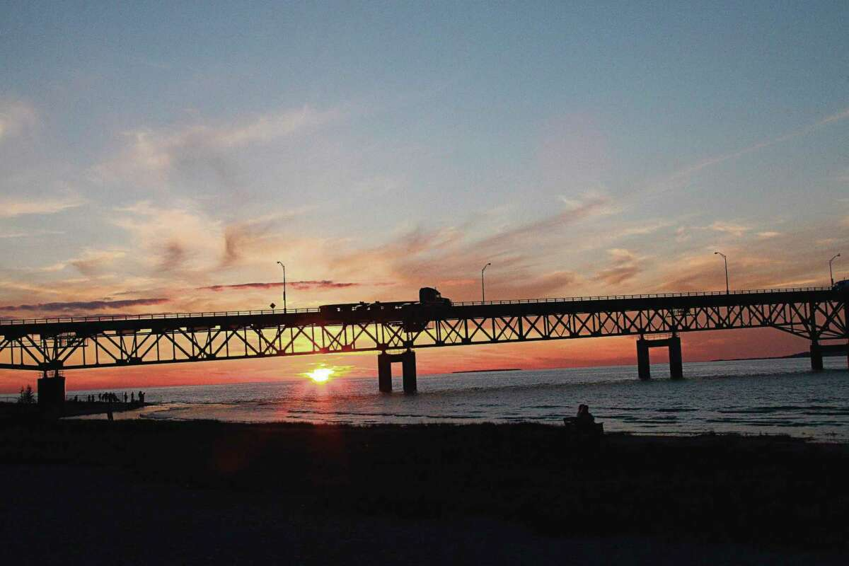 Tourists watch the sun sets over Lake Michigan and behind the Mackinaw Bridge July 28, 2008 as seen from Mackinaw City. (Karen Bleier/AFT via Getty Images)