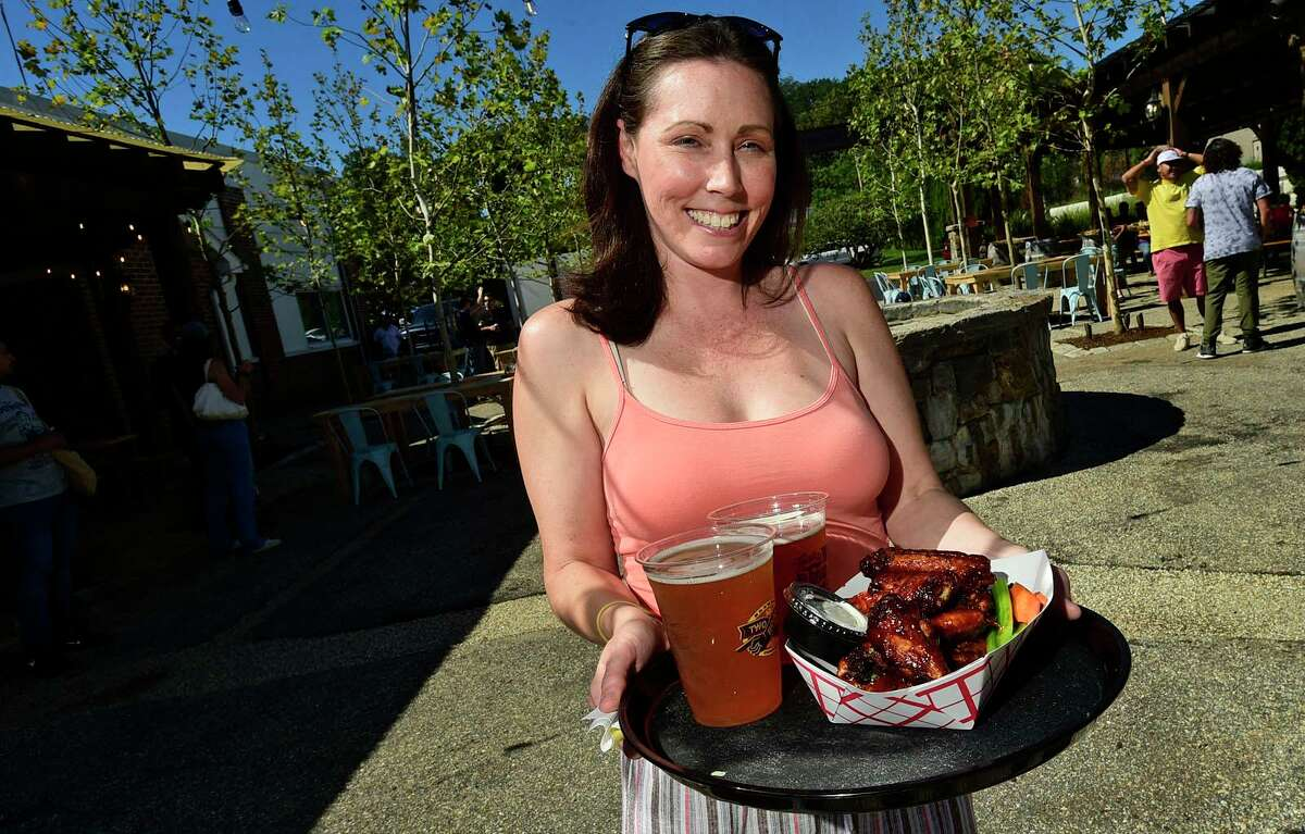 314 Beer Garden Event and Social Media Manager Jennifer Sandusky serves up beer and Mole Wings at their grand opening Saturday, September 25, 2021, in Norwalk, Conn.