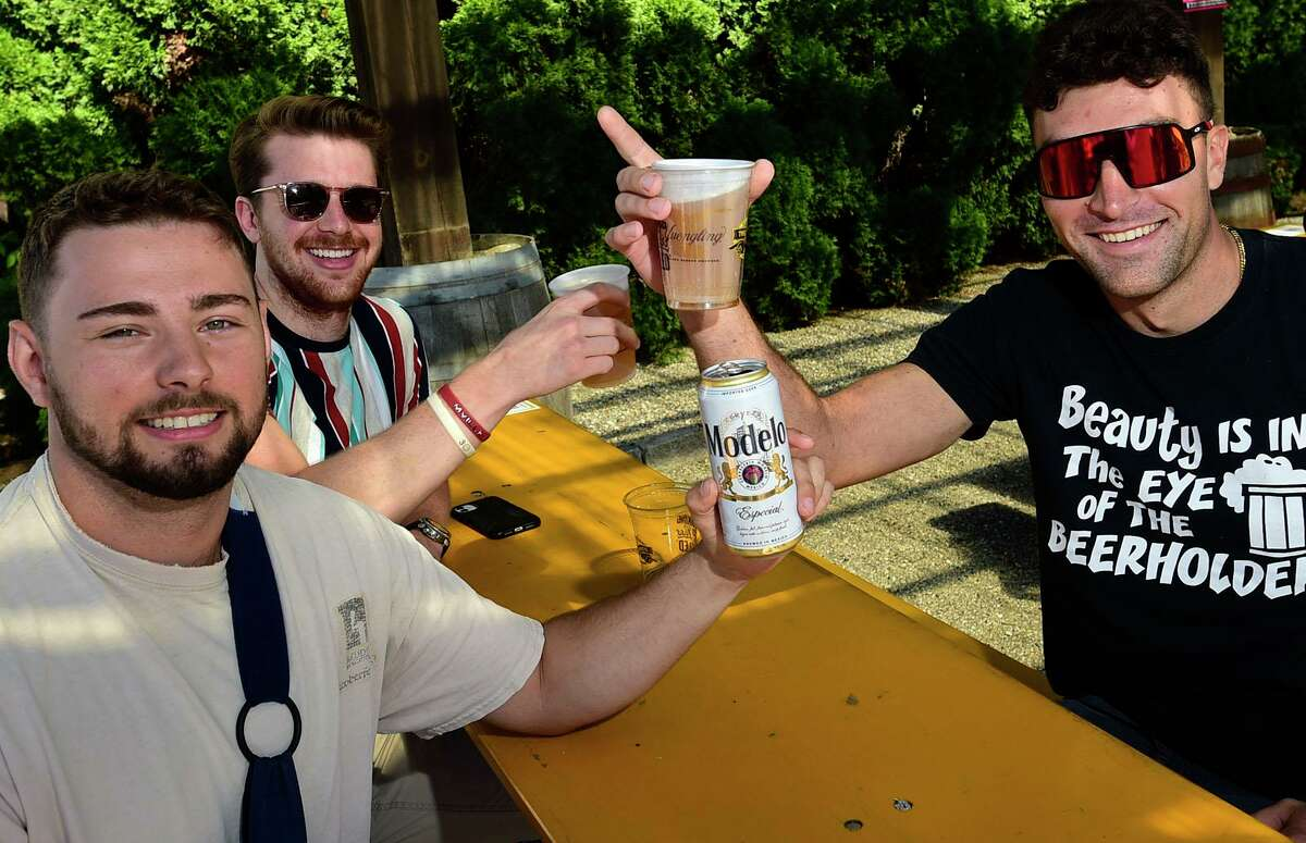 Lewis Grassy of Redding, Tristan Green of Easton and Juan Gomez of Stamford celebrate the 314 Beer Carden grand opening Saturday, September 25, 2021, in Norwalk, Conn.
