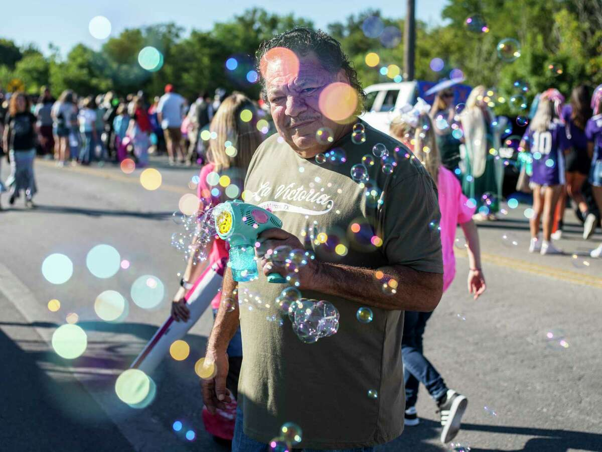 Rogelio Casas, 68, blows bubbles into the crowd before the start of the annual Mermaid Promenade in San Marcos on Saturday. Casas said this was his first year participating in the parade.