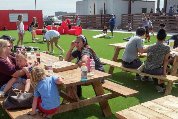 Families and friends enjoy the new outdoor eating, games and football watching 09/25/2021 afternoon at the grand opening of The Tailgate at 4401 N. Big Spring Street. Tim Fischer/Reporter-Telegram