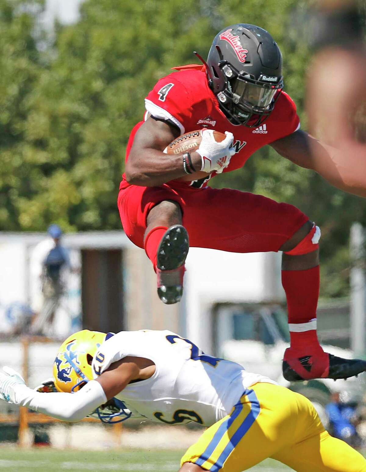 UIW running back Kevin Brown leaps over McNeese Richard Akers in the fourth quarter on Saturday, Sept. 25, 2021.