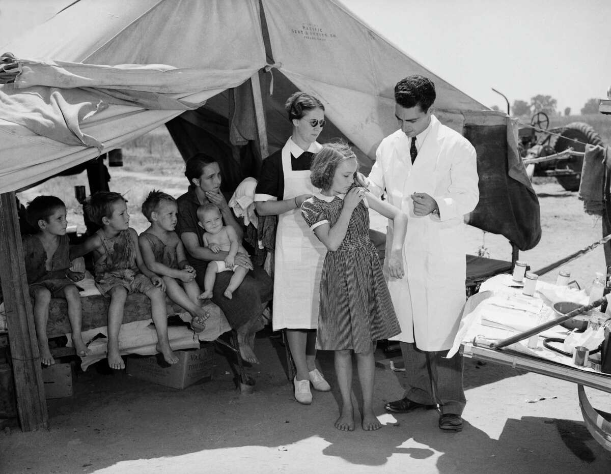 Dr. F.H. Redwell and nurse Clarise Tucker, both of the state health department, immunize a squatter family for smallpox and typhoid fever in 1939. The back of the station wagon serves as shelf for medical equipment.