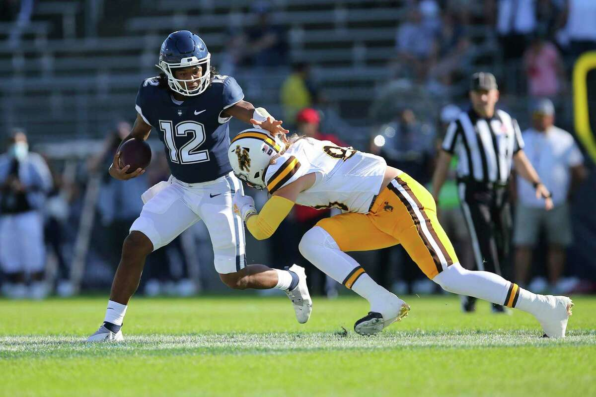 Connecticut quarterback Tyler Phommachanh (12) is tackled by Wyoming defensive end Garrett Crall (88) during the first half of an NCAA football game on Saturday, Sept. 25, 2021, in East Hartford, Conn. (AP Photo/Stew Milne)
