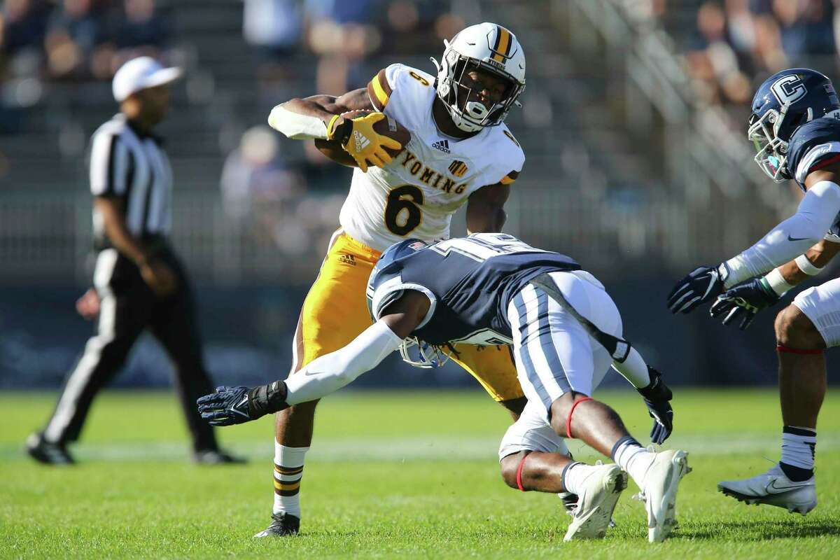 Wyoming running back Xazavian Valladay (6) is tackled by Connecticut defensive back Durante Jones (19) during the first half of an NCAA football game on Saturday, Sept. 25, 2021, in East Hartford, Conn. (AP Photo/Stew Milne)