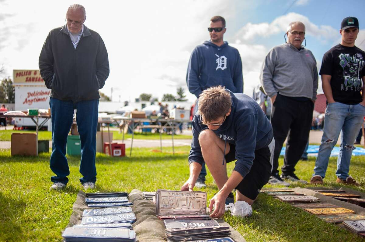 Mount Pleasant resident Mark Wyrick flips through license plates for one of his cars at the Midland Antique Festival on Sept. 25, 2021 at the Midland County Fairgrounds. The festival returned after an 18-month hiatus. (Andrew Mullin/amullin@hearstnp.com)