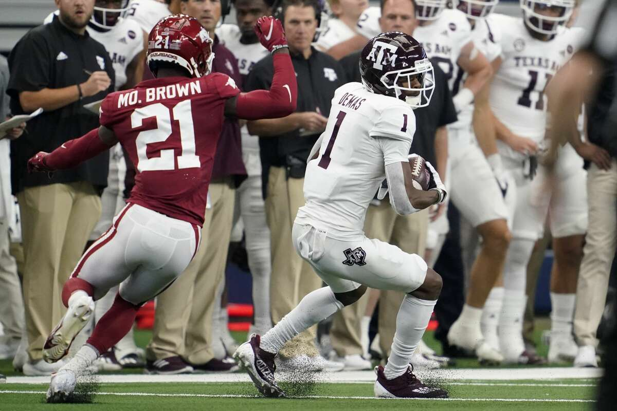 Texas A&M wide receiver Demond Demas (1) catches a pass in front of Arkansas defensive back Montaric Brown (21) in the first half of an NCAA college football game in Arlington, Texas, Saturday, Sept. 25, 2021. (AP Photo/Tony Gutierrez)