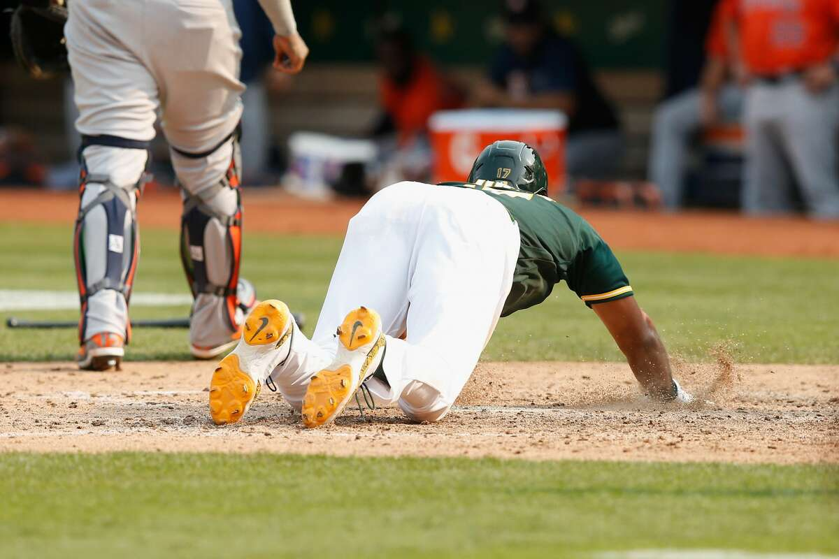 OAKLAND, CALIFORNIA - SEPTEMBER 25: Elvis Andrus #17 of the Oakland Athletics slides into home plate after injuring himself while scoring the winning run on a double by Starling Marte #2 in the bottom of the ninth inning against the Houston Astros at RingCentral Coliseum on September 25, 2021 in Oakland, California. (Photo by Lachlan Cunningham/Getty Images)