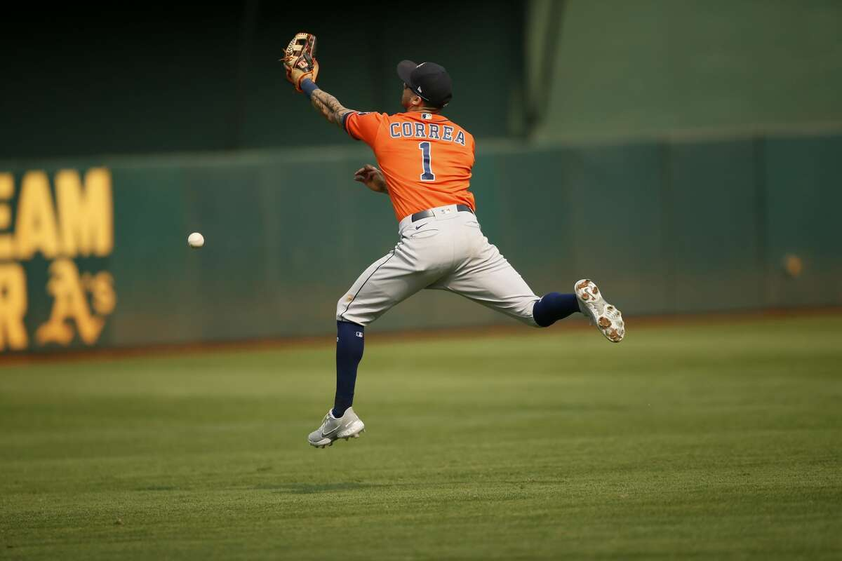 Houston Astros shortstop Carlos Correa (1) misses the catch for an RBI single by Athletics' Josh Harrison (1) in the seventh inning during an MLB game at RingCentral Coliseum on Saturday, Sept. 25, 2021, in Oakland, Calif.