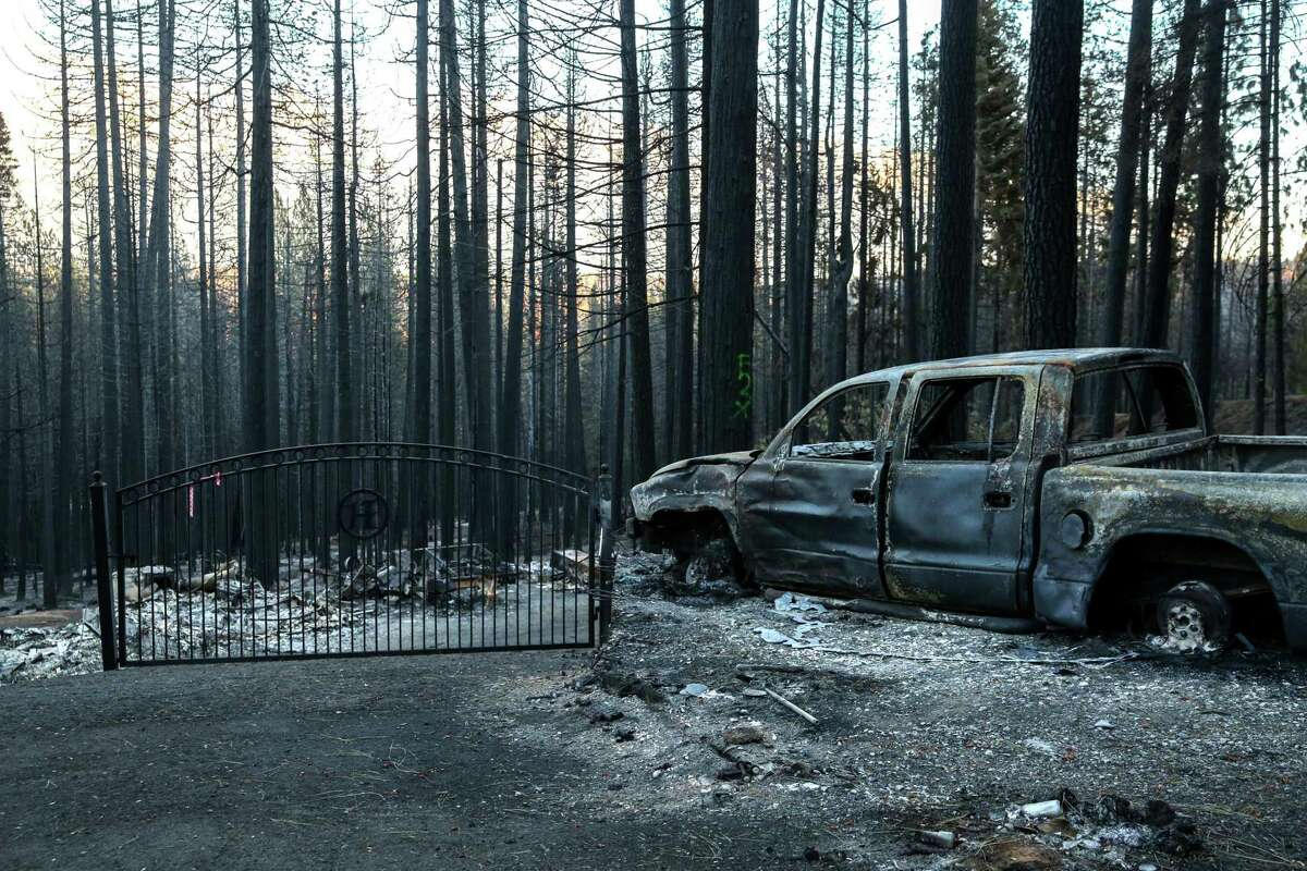 A charred vehicle sits near the entrance gate to the once-standing home of Tabatha and Jeffrey Walker in Grizzly Flats (El Dorado County). The couple lost their home to the Caldor Fire.