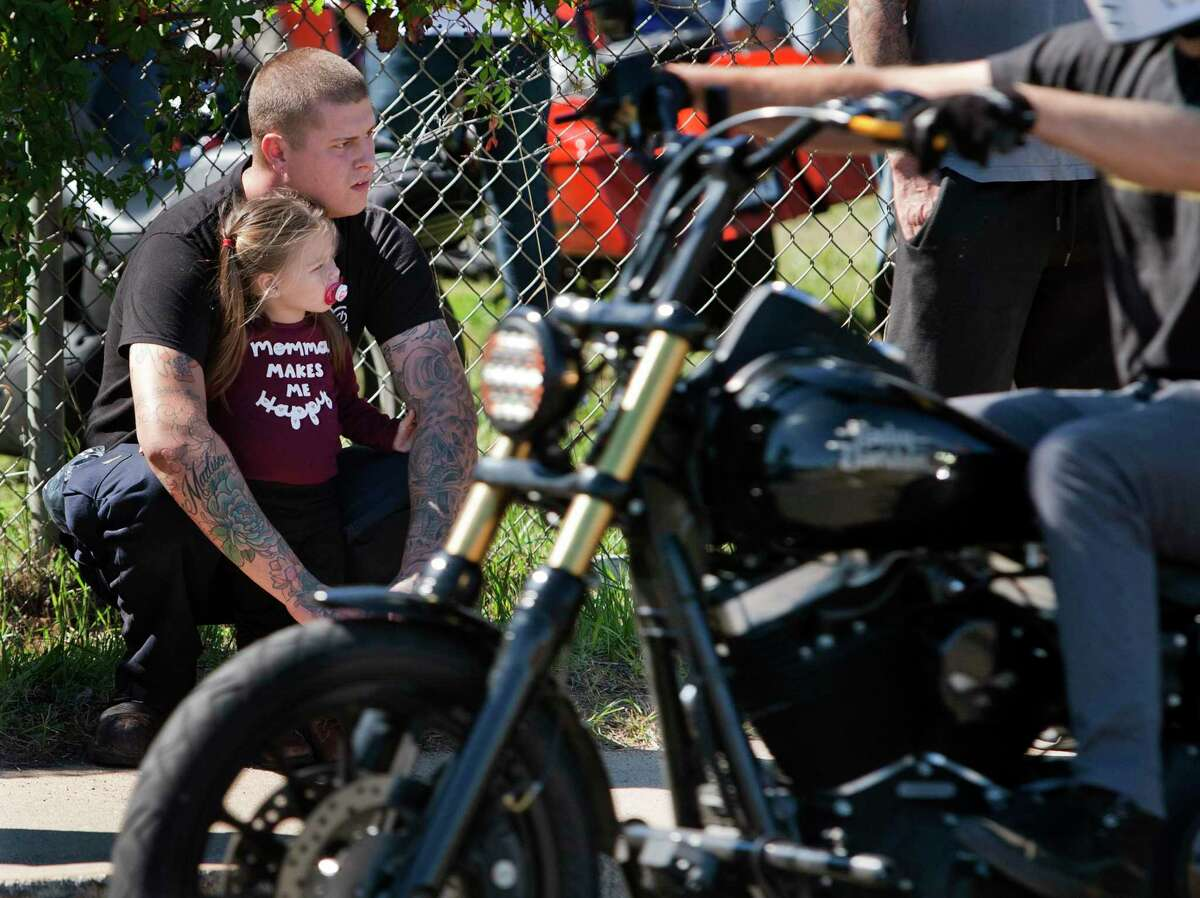 Jeremy Verses and his daughter Maddie, 2, watch as bikers descend on the city as part of EastCoastin' 2021 in New Haven on Saturday.