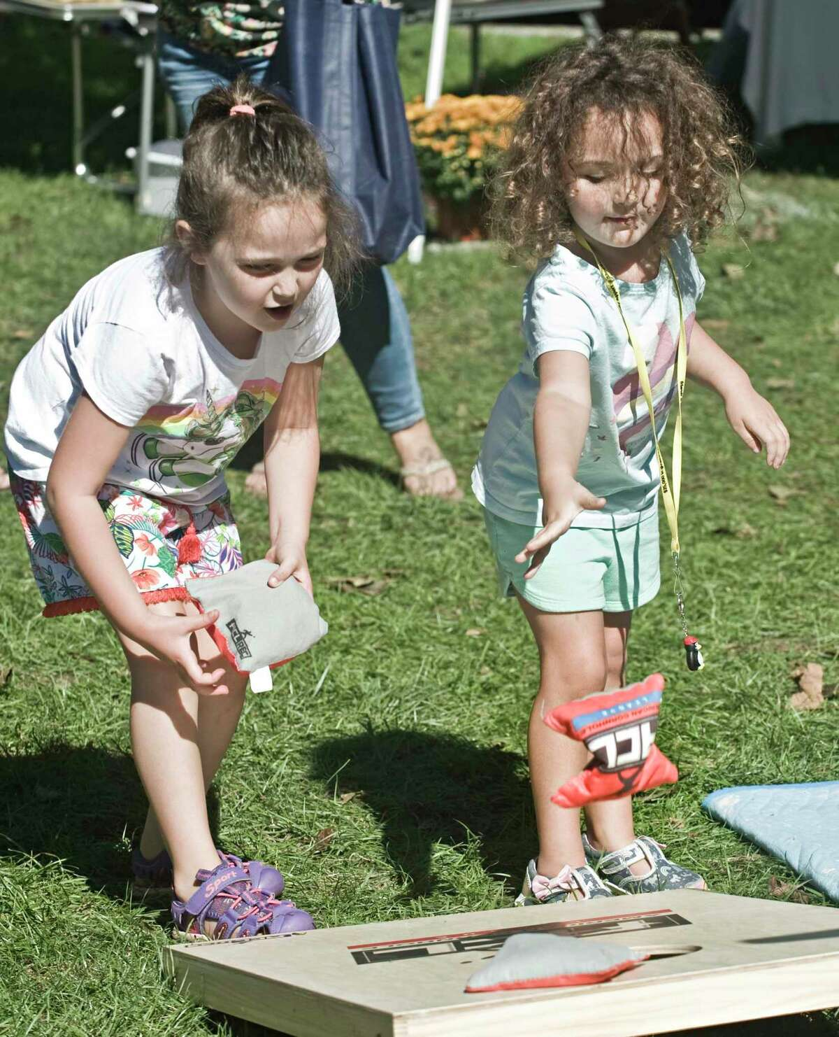 Taylor DeDiase, 6 of Brookfield, and her sister Remi, 4, doing the bean bag game at the Apple Festival on the New Milford town green. Saturday, Sept. 25, 2021