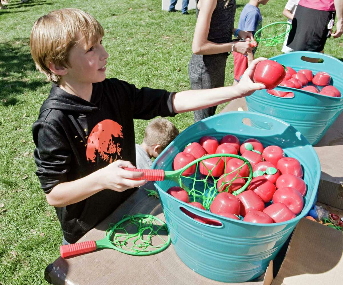 Mason Breidster, 8 of New Milford, looks for a prize at the apple bobbing event during the Apple Festival on the New Milford town green. Saturday, Sept. 25, 2021