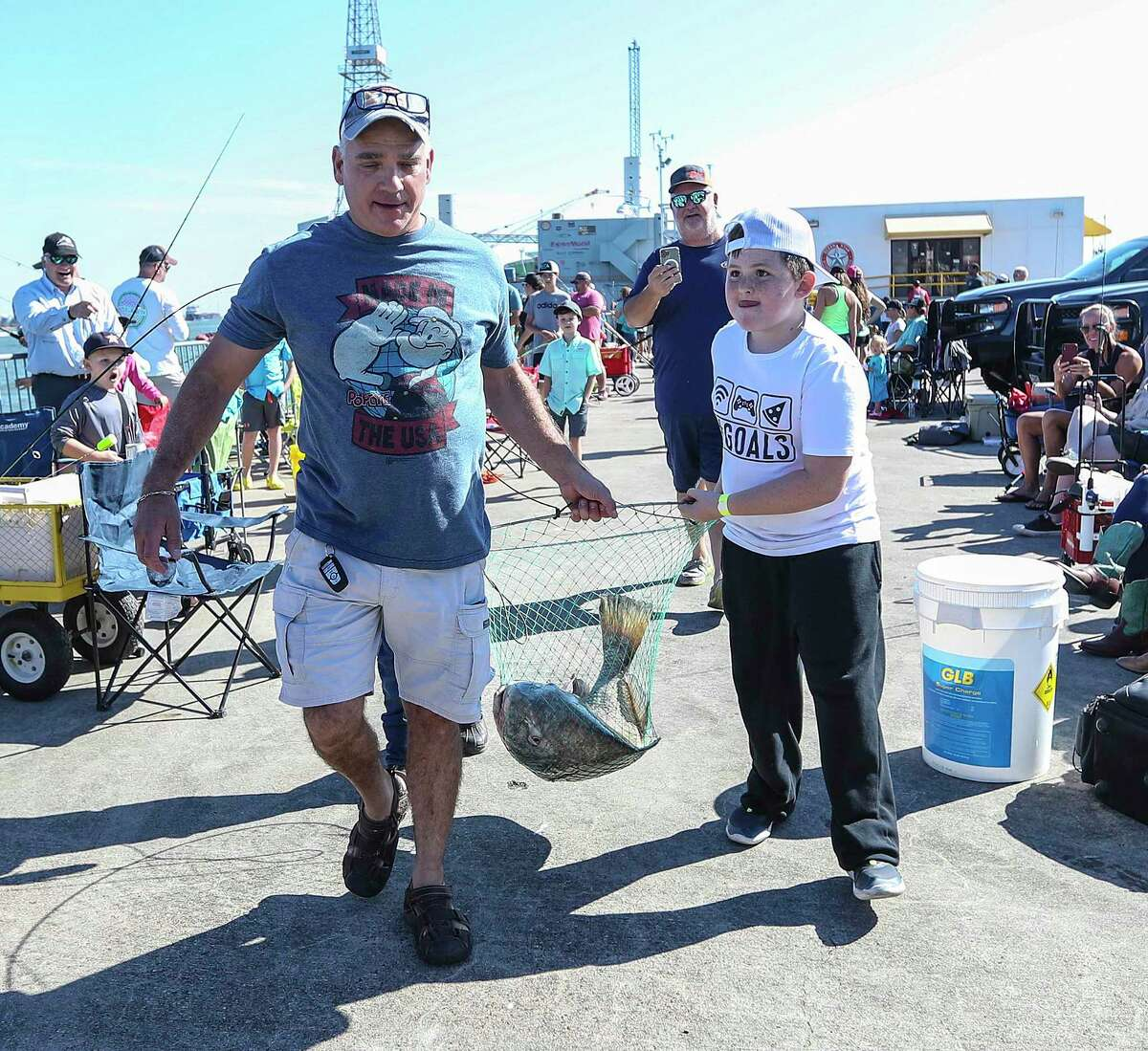 Teagan Taylor, 8, and his stepfather, Paul Hickman, carry a 32-pound black drum during the Cast Away Rods Guppy Cup KidFish in Galveston on Saturday. Teagan was a winner in his age category for the fish, which was weighed and released.