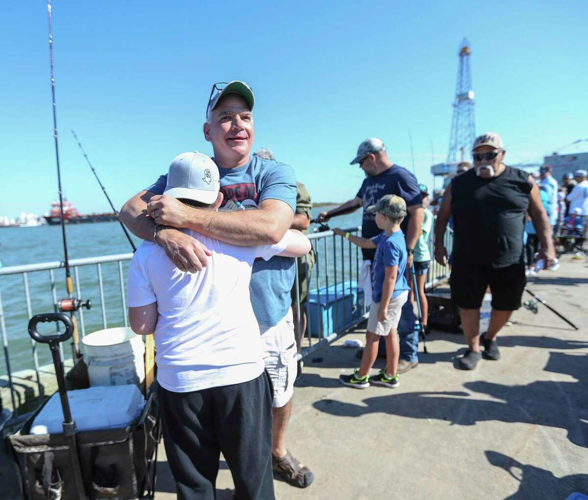 Teagan Taylor, 8, gets a hug from his step-dad, Paul Hickman, after Taylor hauled in a 32-pound black drum fish (which was the largest fish of the tournament) during the 3rd annual Cast Away Rods Guppy Cup KidFish, Saturday, September 25, 2021, in Galveston. It was weighed and released.
