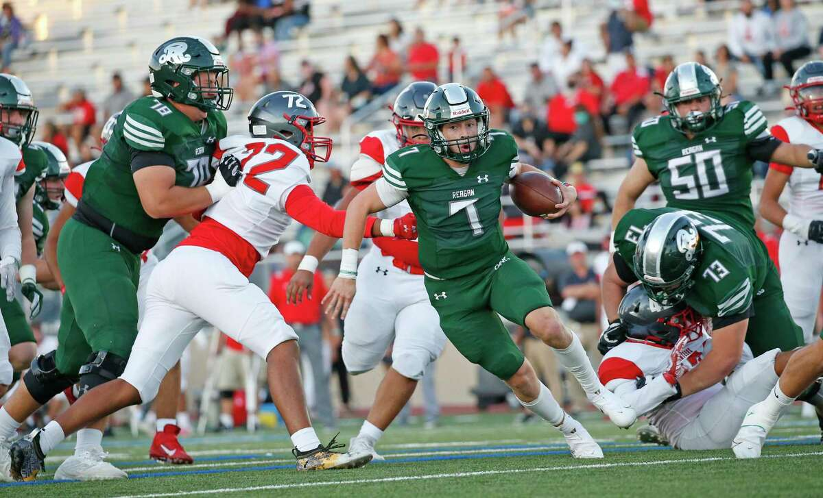 Regan quarterback Britton Moore elude tacklers on his touchdown run in first quarter on Saturday, Sept. 25, 2021. Halftime score Reagan 35 Lee 0