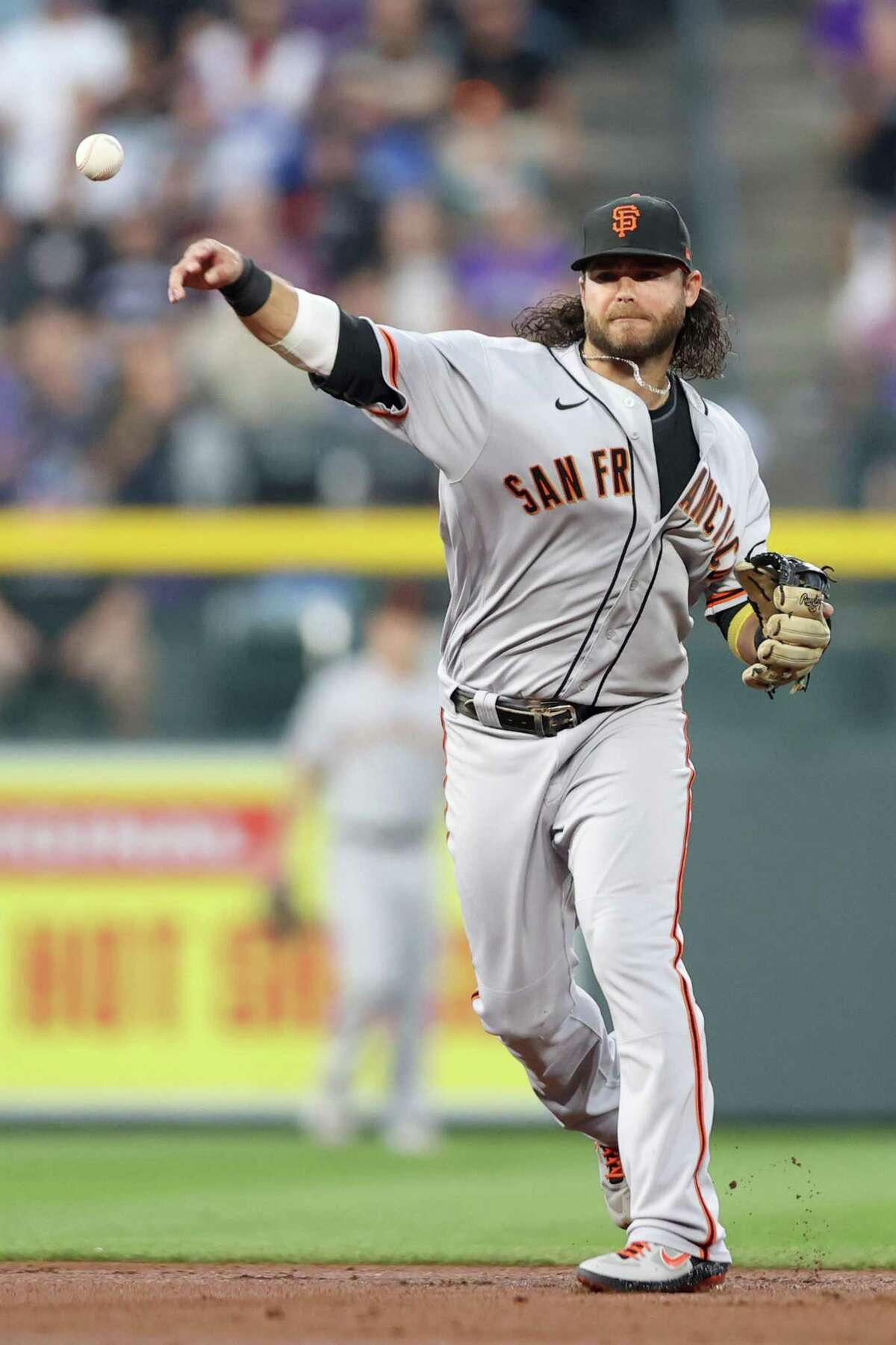 DENVER, COLORADO - SEPTEMBER 25: Brandon Crawford #35 of the San Francisco Giants throws out Raimel Tapia the Colorado Rockies in the first inning at Coors Field on September 25, 2021 in Denver, Colorado. (Photo by Matthew Stockman/Getty Images)