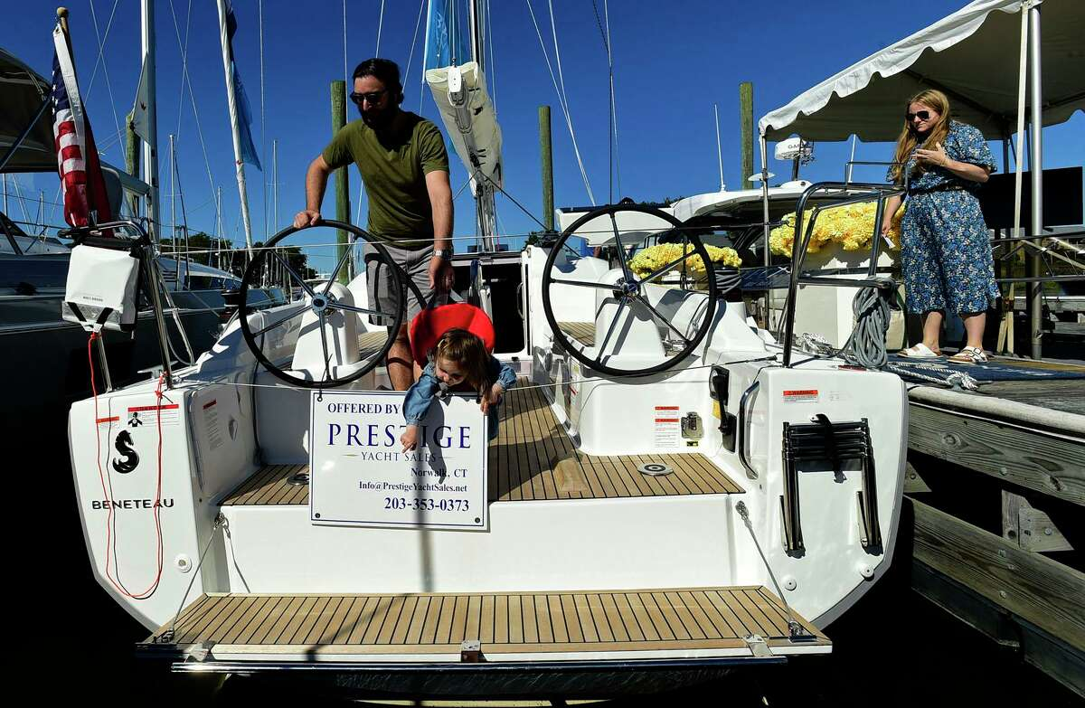 Visitors including Lou Cona, his daughter Isabella Cona, 1, and wife Laura Cona of Darien, browse watercraft like the Beneteau dual helm sailboat at The Norwalk Boat Show Saturday, September 25, 2021, at Cove Marina in Norwalk, Conn.