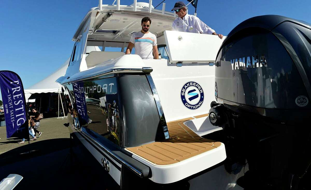 Visitors including Greg Smith odf Stamford browse watercraft including the Southport 33DC with Prestige sale associate Whit Miller at The Norwalk Boat Show Saturday, September 25, 2021, at Cove Marina in Norwalk, Conn.