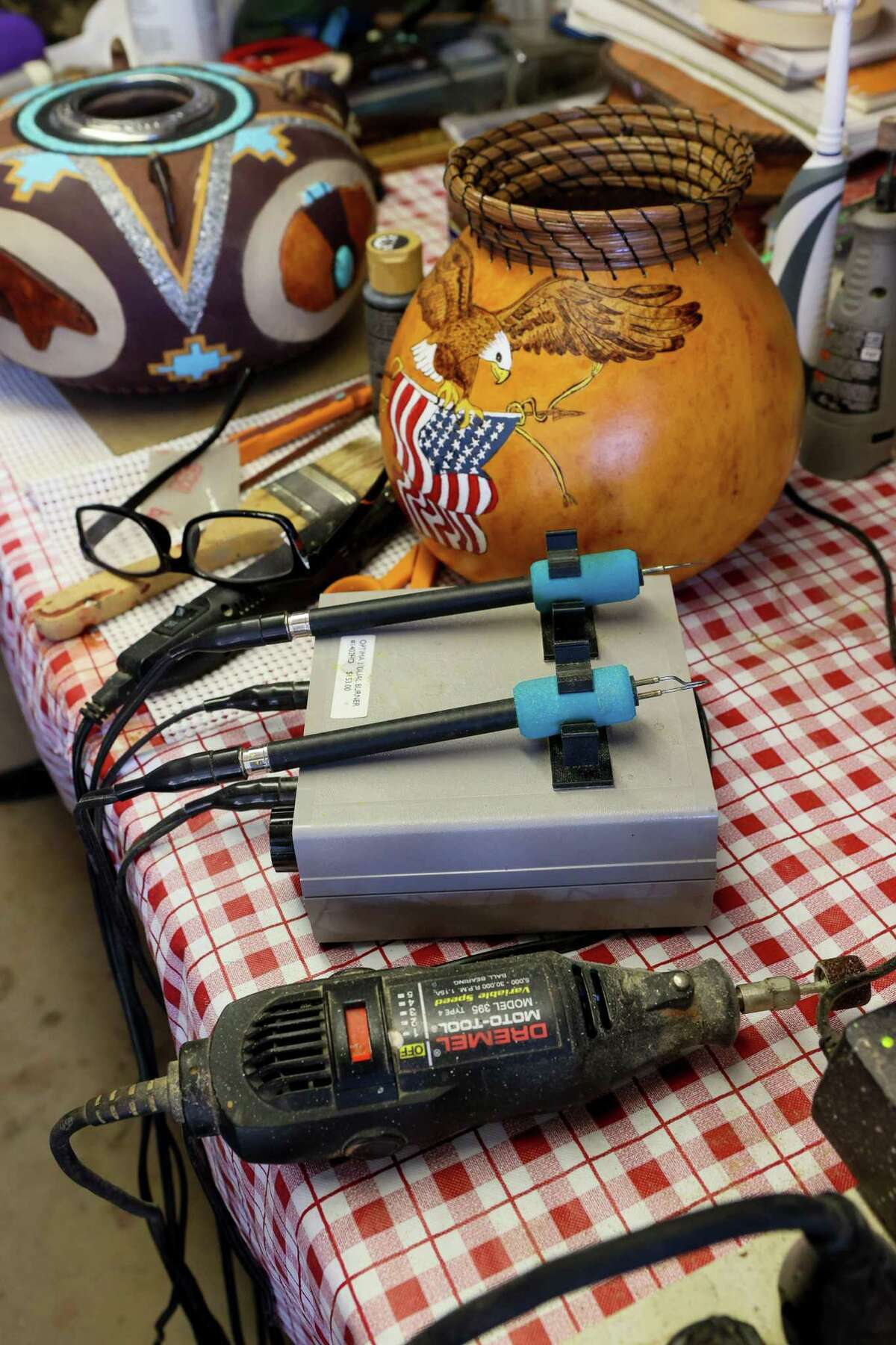 Converse resident David Cleaveland uses burners, center, for cutting and edging straight lines in gourds, and a Dremel tool, below,for sanding in his workshop garage on Friday, Sept. 17.