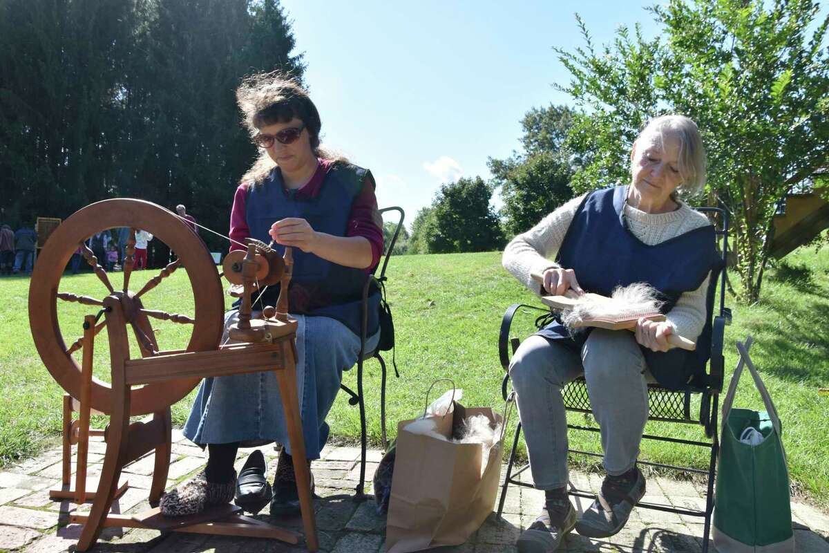 (From left) Jessica Smith and Sue Lundquist are two of the local residents who volunteered to show visitors to G&D Alpaca Farm on Saturday how spinning and hand carding of alpaca wool works in the overall process to creating yarn. (Arielle Breen/News Advocate)