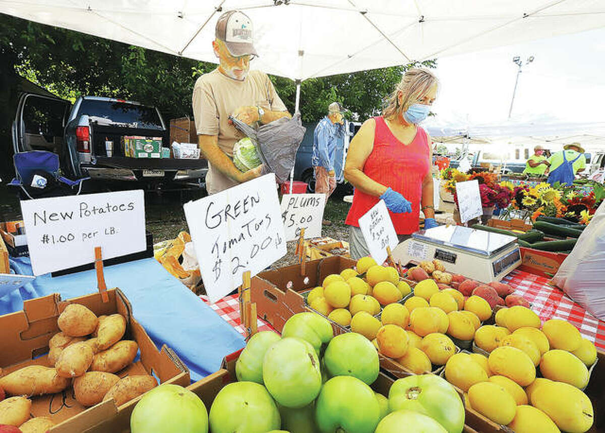 Raymond and Corky Gress wait on a customer at the Jerseyville Farmer's Market held on the lot at 902 S. State St. in Jerseyville in 2020. The final market of the season is planned 4-7 p.m. Tuesday.