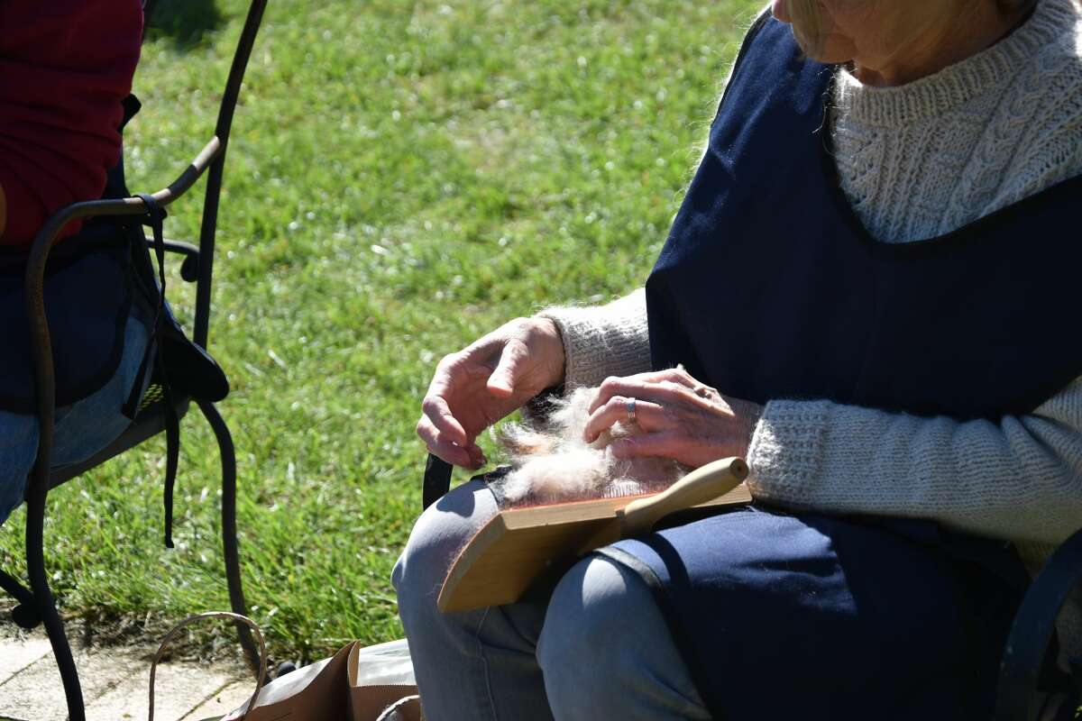 Sue Lundquist demonstrates carding wool to visitors to G&D Alpaca Farm on Saturday.