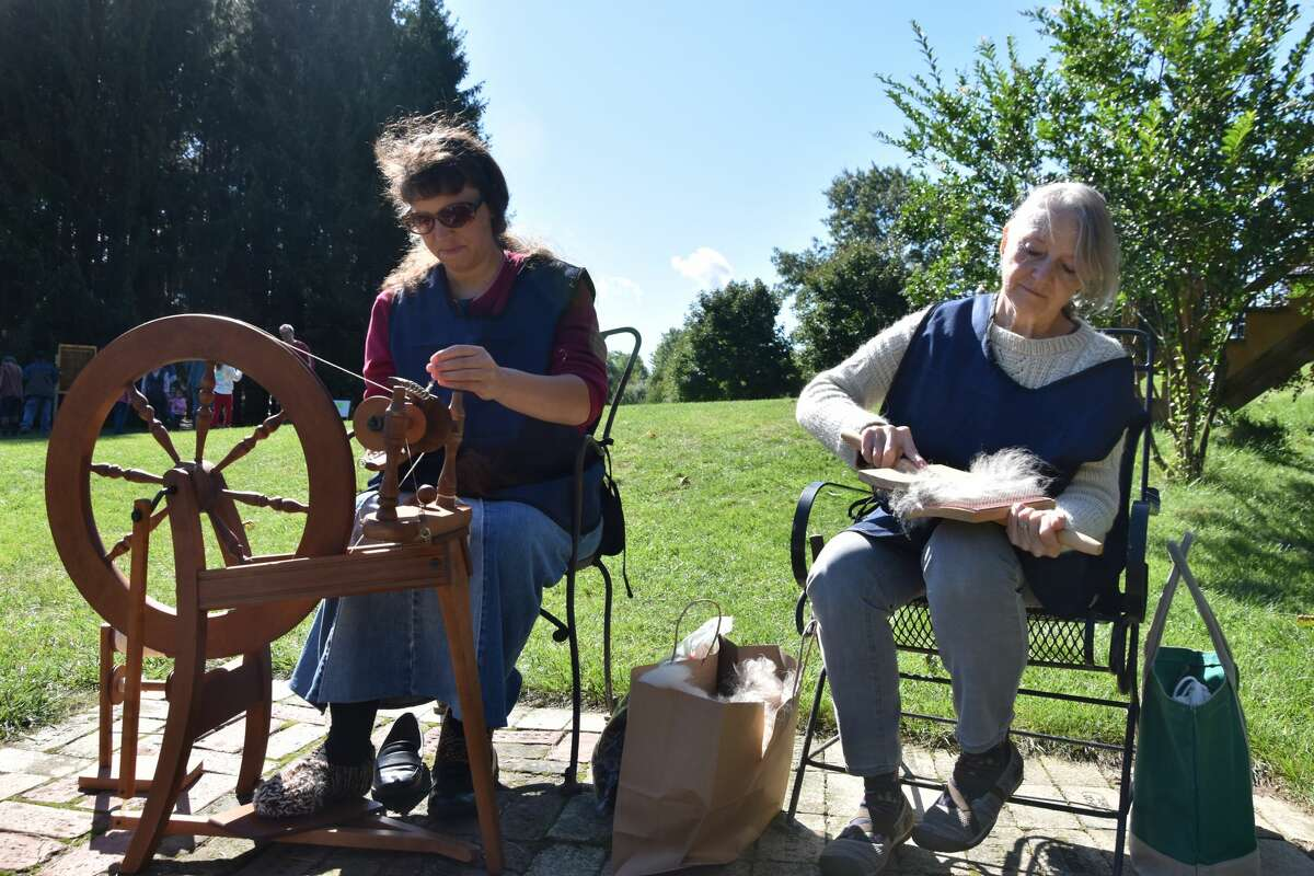 (From left) Jessica Smith and Sue Lundquist are two of the local residents who volunteered to show visitors to G&D Alpaca Farm on Saturday how spinning and hand carding of alpaca wool works in the overall process to creating yarn.