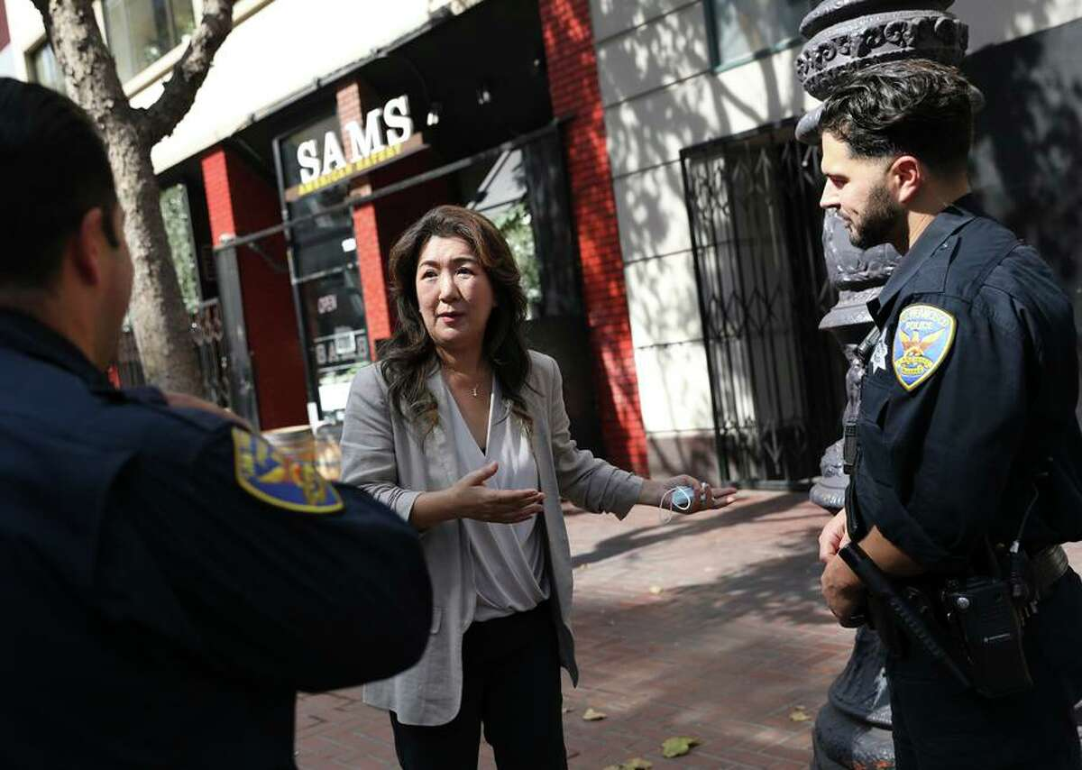 Jeannie Kim, who owns Sam's American Eatery at 1220 Market St., visits with two officers. The restaurateur says she spends 25% of her time dealing with vandalism and other crime.