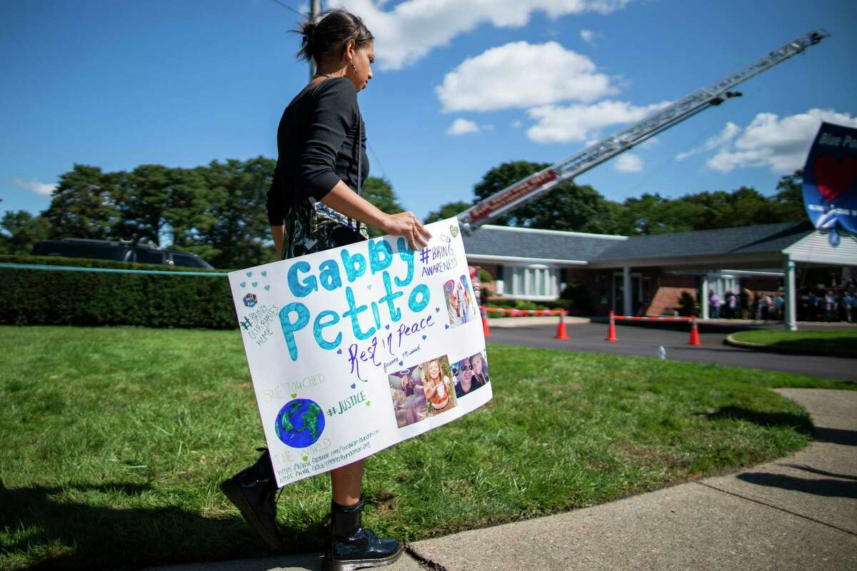 A woman carries a placard in honor of Petito as people attend the funeral service of Gabby Petito at Moloney's Funeral Home in Holbrook, N.Y. Sunday, Sept. 26, 2021.