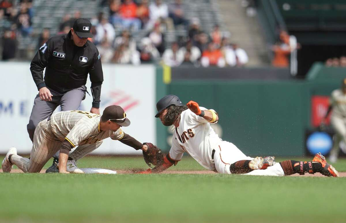 The Giants' Brandon Crawford is tagged by the Padres' Adam Frazier at second while trying to stretch a single on Sept. 16.