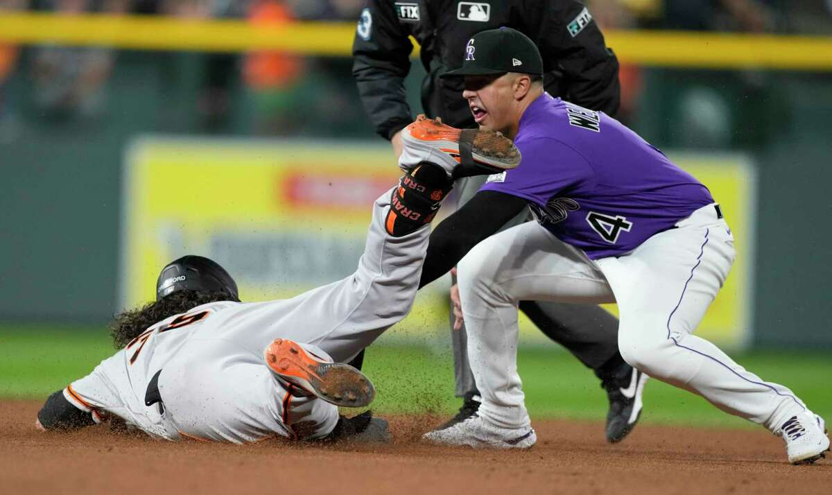 Colorado Rockies third baseman Colton Welker, right, tags out San Francisco Giants' Brandon Crawford, left, at second base as Crawford tried to stretch a single into a double in the eighth inning of a baseball game Friday, Sept. 24, 2021, in Denver. (AP Photo/David Zalubowski)