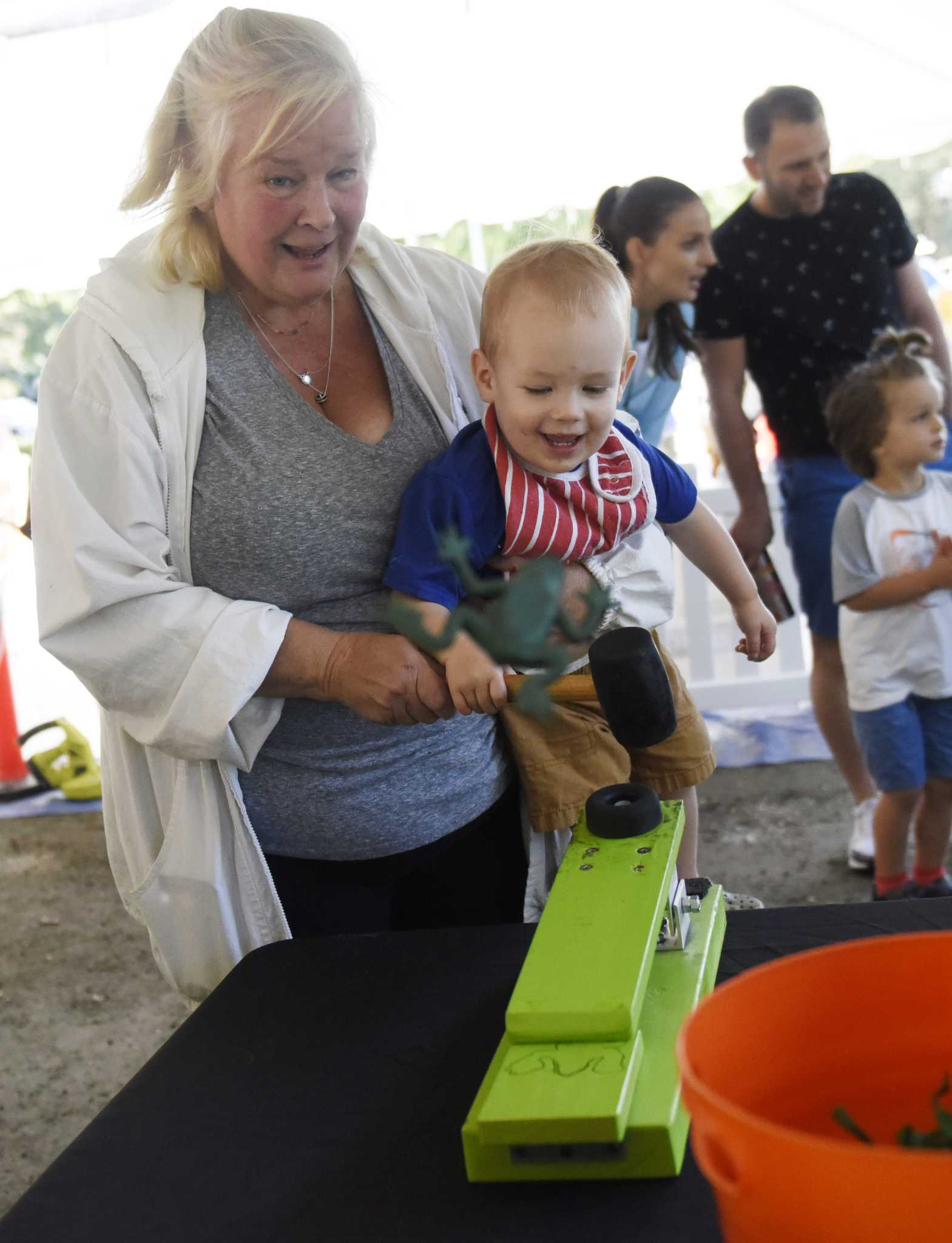 Stamford's Peggy Gray and her grandson, Casey, 1, try their luck on the frog flinger at the first of three Fall Family Fest Sundays at the Stamford Museum & Nature Center in Stamford, Conn. Sunday, Sept. 26, 2021. To celebrate the season, the Museum & Nature Center held a mini festival with added attractions, enhanced programming, and fun offerings for the whole family. The event continues on Oct. 3 and Oct. 17.