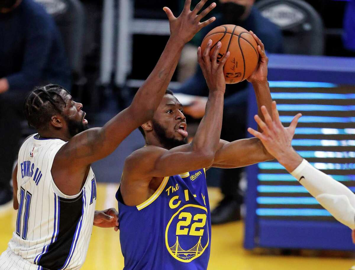 Golden State Warriors' Andrew Wiggins shoots against Orlando Magic's James Ennis in 2nd quarter during NBA game at Chase Center in San Francisco, Calif., on Thursday, February 11, 2021.