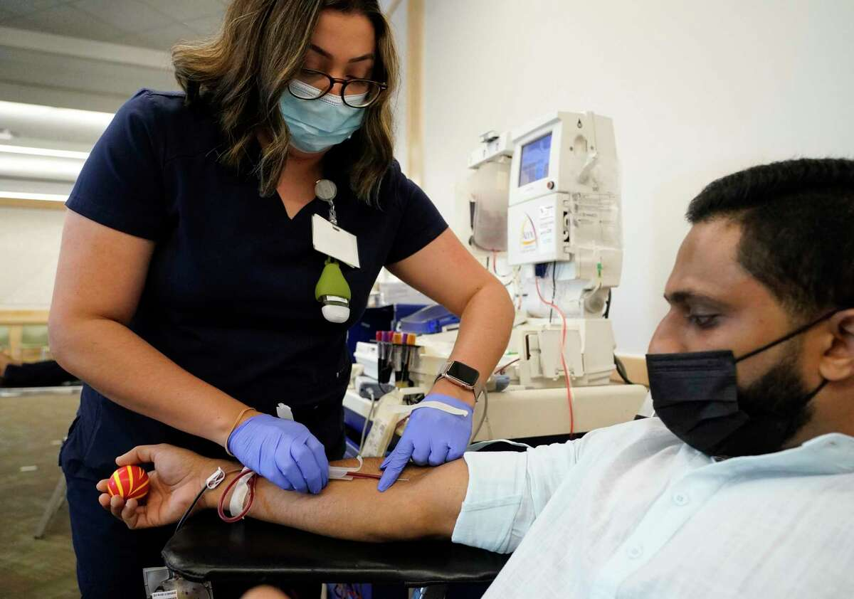 Crystal Duran, a phlebotomist with Gulf Coast Regional Blood Center, left, works with Joyab Prasla of Spring as he gives blood at Ismaili Jamatkhana, 24525 Community Center Dr., Sunday, Sept. 26, 2021 in Spring. Ismaili Muslims across the world are hold their Global Civic Day on Sunday. In the Houston area, Ismailis are holding blood drives.