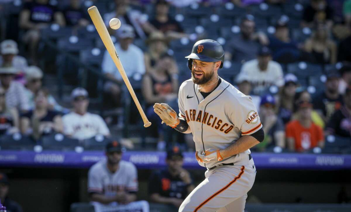 San Francisco Giants' Brandon Belt is hit by a pitch from Colorado Rockies reliever Lucas Gilbreath in the seventh inning of a baseball game in Denver, Sunday, Sept. 26, 2021.