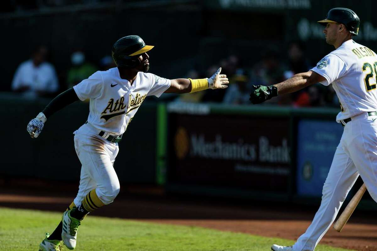 Oakland Athletics' Tony Kemp, left, celebrates with Matt Olson after scoring a run against the Houston Astros in the seventh inning of a baseball game in Oakland, Calif., Sunday, Sept. 26, 2021. (AP Photo/John Hefti)
