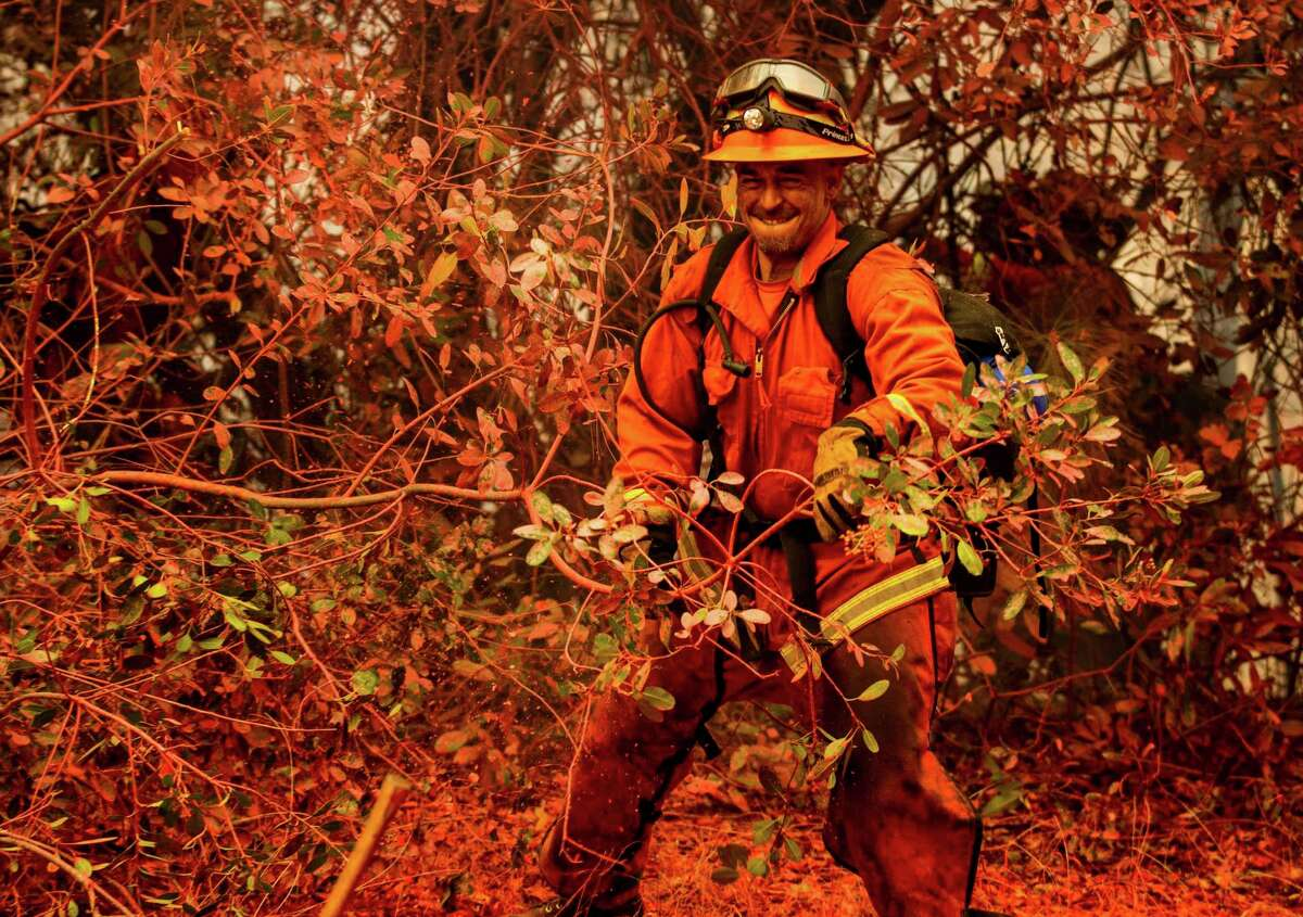 A firefighter clears brush Thursday while battling the Fawn Fire burning north of Redding in Shasta County.