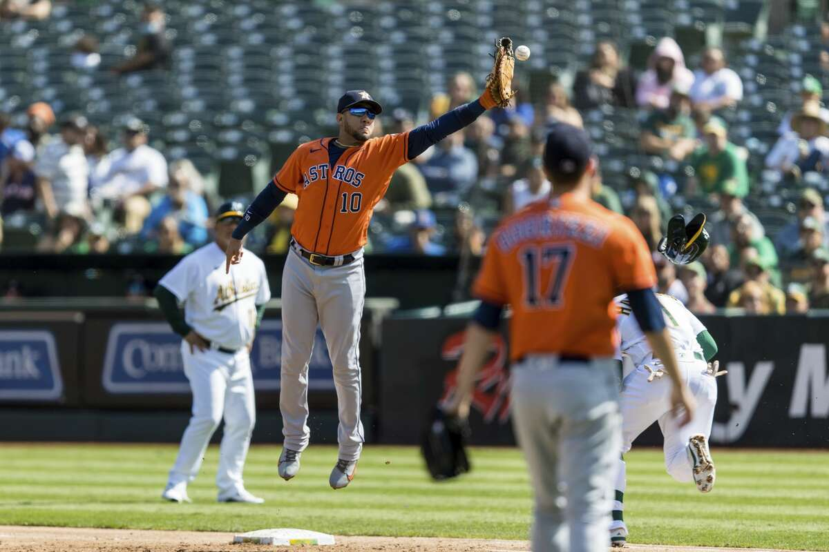 Houston Astros first baseman Yuli Gurriel (10) misses the throw, allowing Oakland Athletics' Josh Harrison, obscured, to reach second base in the third inning of a baseball game in Oakland, Calif., Sunday, Sept. 26, 2021. (AP Photo/John Hefti)