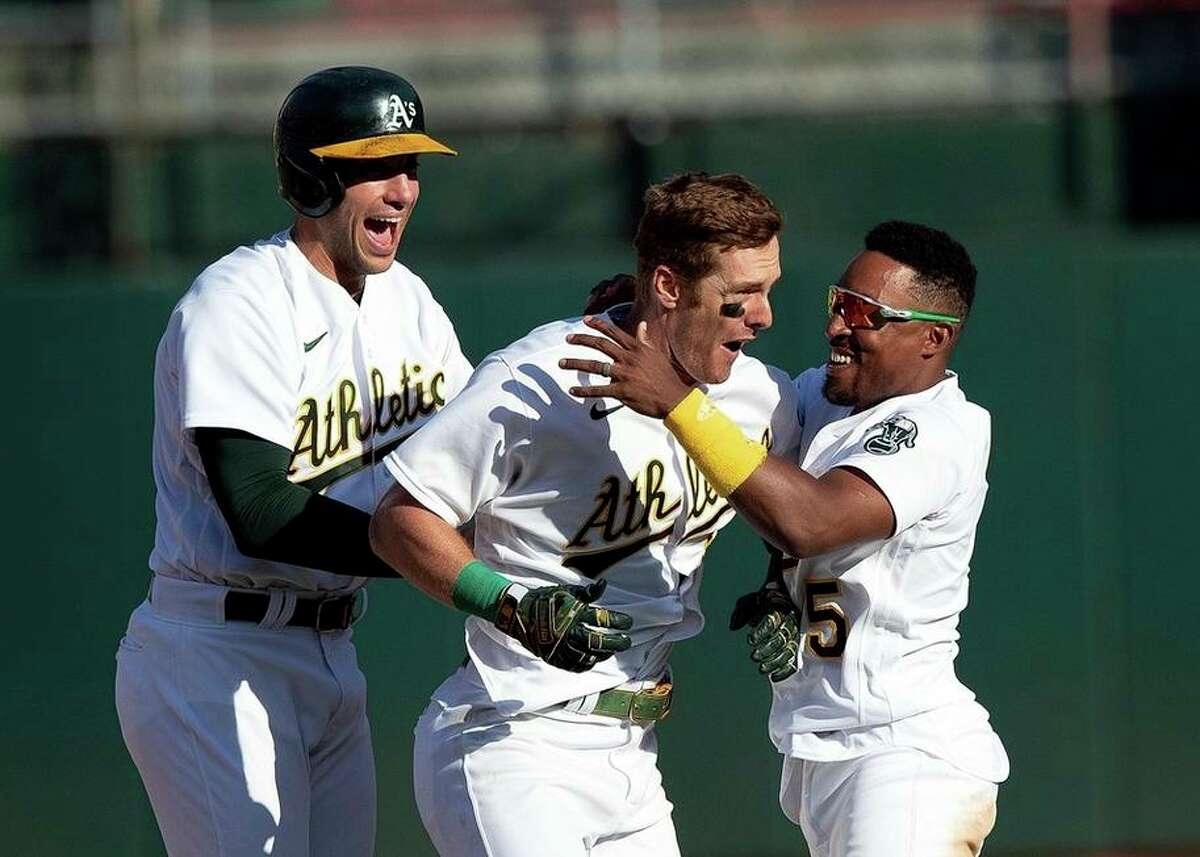 The A's Mark Canha (center) is congratulated by Matt Olson (left) and Tony Kemp after hitting a walk-off single.