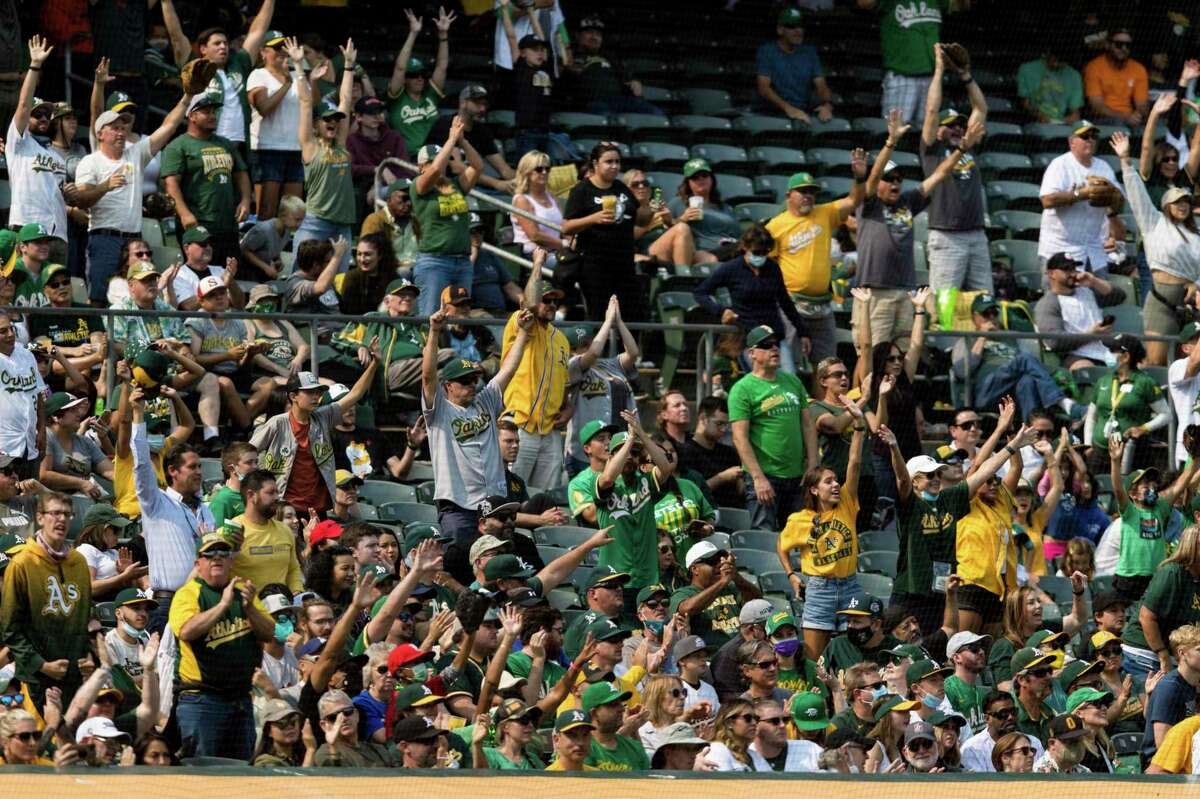 Spectators cheering in the fifth inning of a baseball game between the Oakland Athletics and the Houston Astros in Oakland, Calif., Saturday, Sept. 25, 2021. (AP Photo/John Hefti)