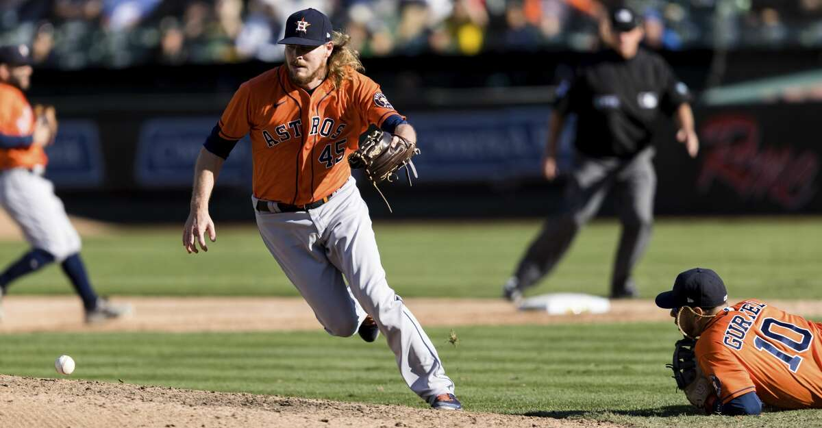 Houston Astros relief pitcher Ryne Stanek (45) loses possession of an infield ball, allowing a Oakland Athletics batter to reach in the ninth inning of a baseball game in Oakland, Calif., Sunday, Sept. 26, 2021. The Athletics won 4-3. (AP Photo/John Hefti)
