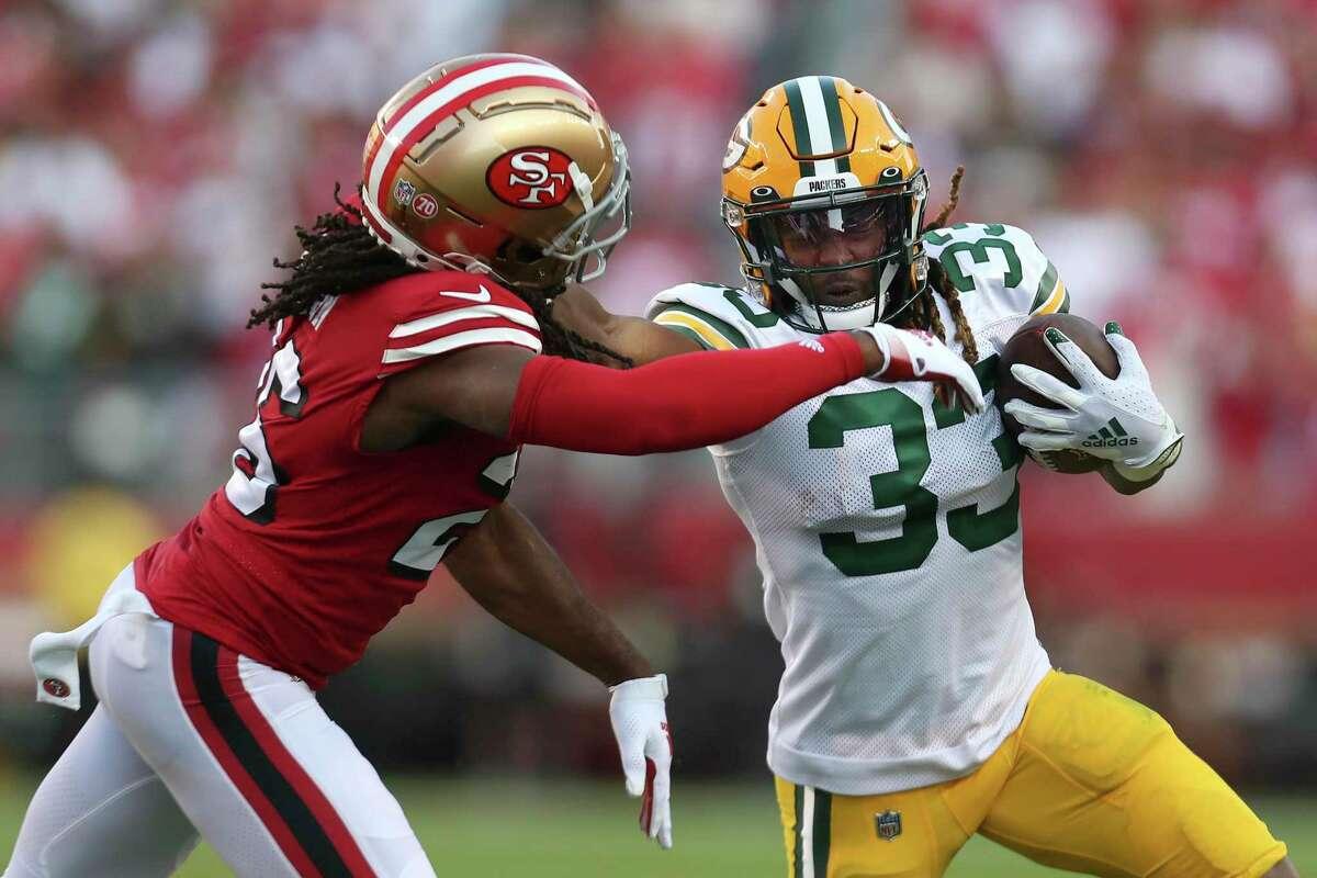 Green Bay Packers running back Aaron Jones (33) runs against San Francisco 49ers cornerback Josh Norman during the first half of an NFL football game in Santa Clara, Calif., Sunday, Sept. 26, 2021. (AP Photo/Jed Jacobsohn)