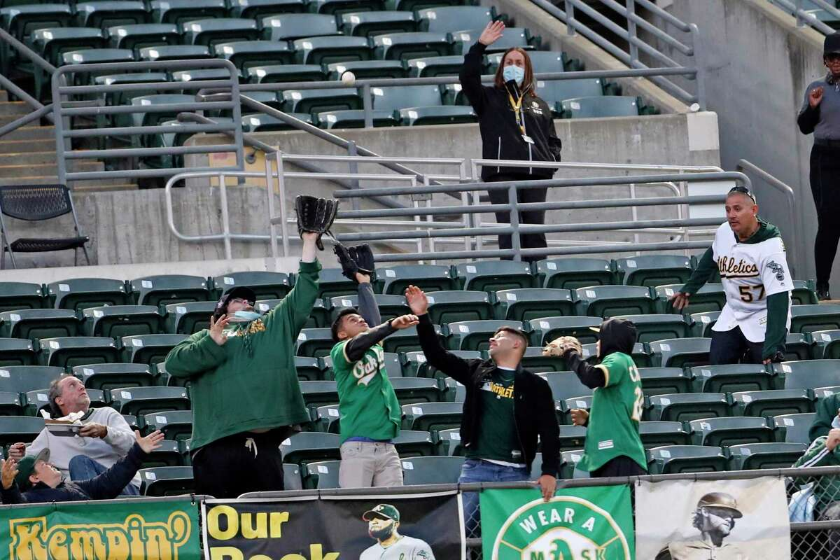 Oakland Athletics' fans reach for Yan Gomes' 4th inning solo home run against Seattle Mariners during MLB game at Oakland Coliseum in Oakland, Calif., on Monday, August 23, 2021.