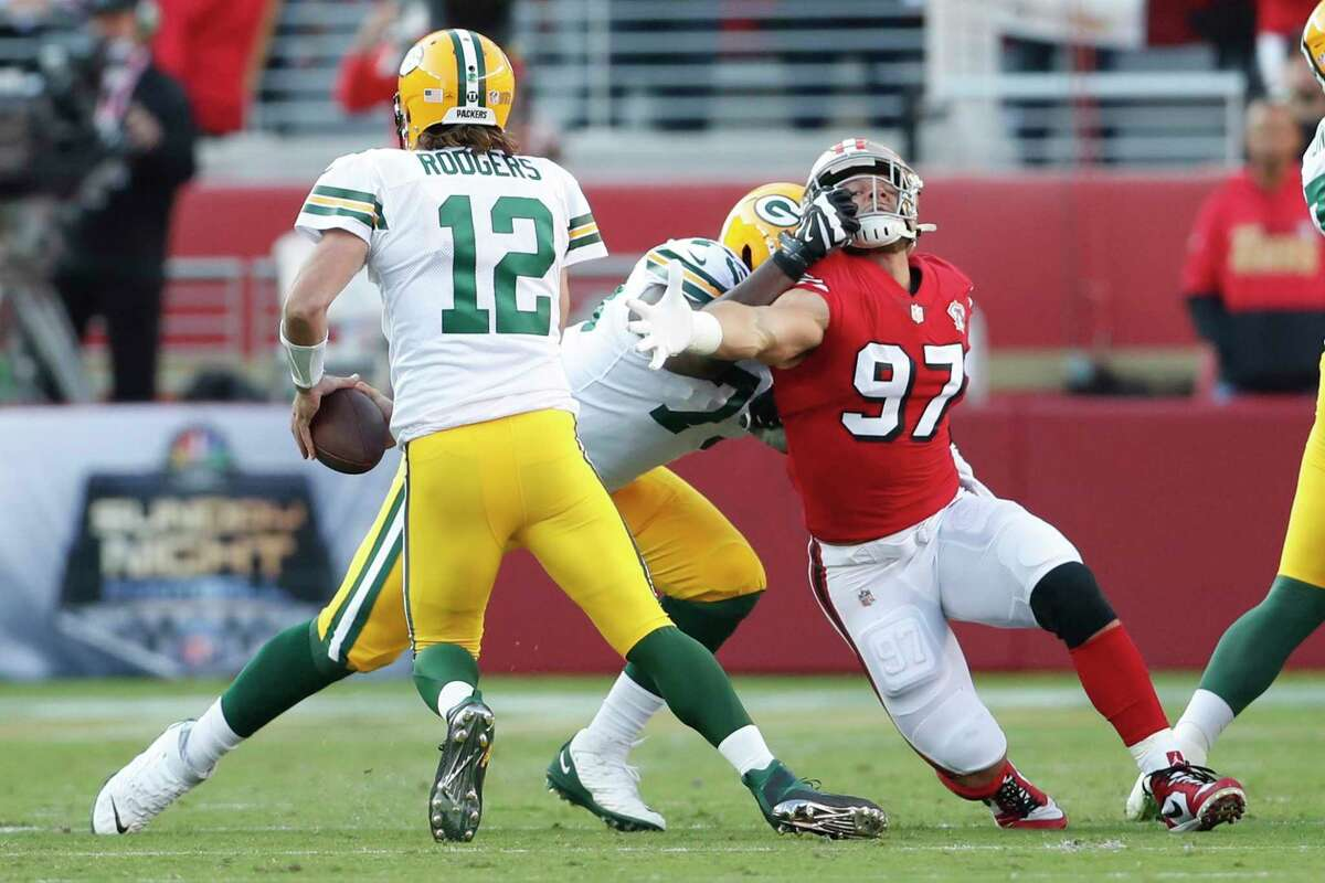 San Francisco 49ers' Nick Bosa is held as Green Bay Packers' Aaron Rodgers looks to scramble in 1st quarter during NFL game at Levi's Stadium in Santa Clara, CA on Sunday, September 26, 2021.