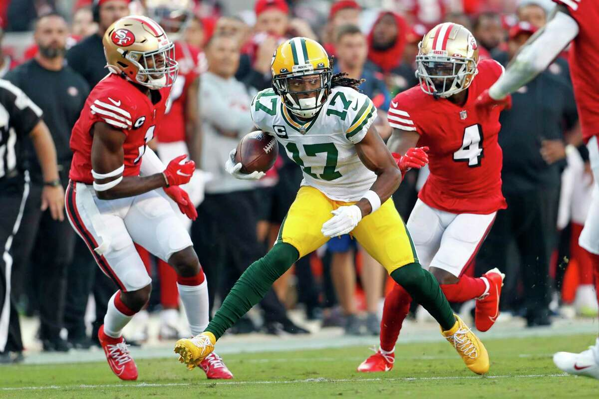 Packers wide receiver Davante Adams tries to elude Jimmie Ward and Emmanuel Moseley in the second quarter.