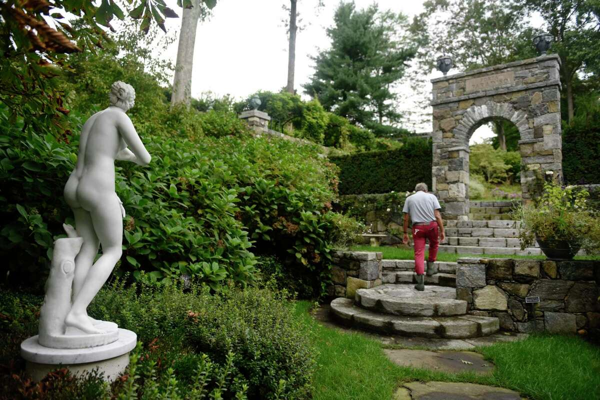 """Fred Landman walks past a marble statue through the Porta Paradiso section of the sprawling 13-acre Sleepy Cat Farm in Greenwich, Conn. Thursday, Sept. 16, 2021. Landman acquired the Georgian Revival house and grounds in 1994 and collaborated with Greenwich architect Charles Hilton and landscape architect Charles J. Stick to create a majestic and magical garden that would come to be known as Sleepy Cat Farm. The property will be the subject of a book """"Sleepy Cat Farm: A Gardener's Journey,"""" to be released Oct. 19 by Monacelli Press."""