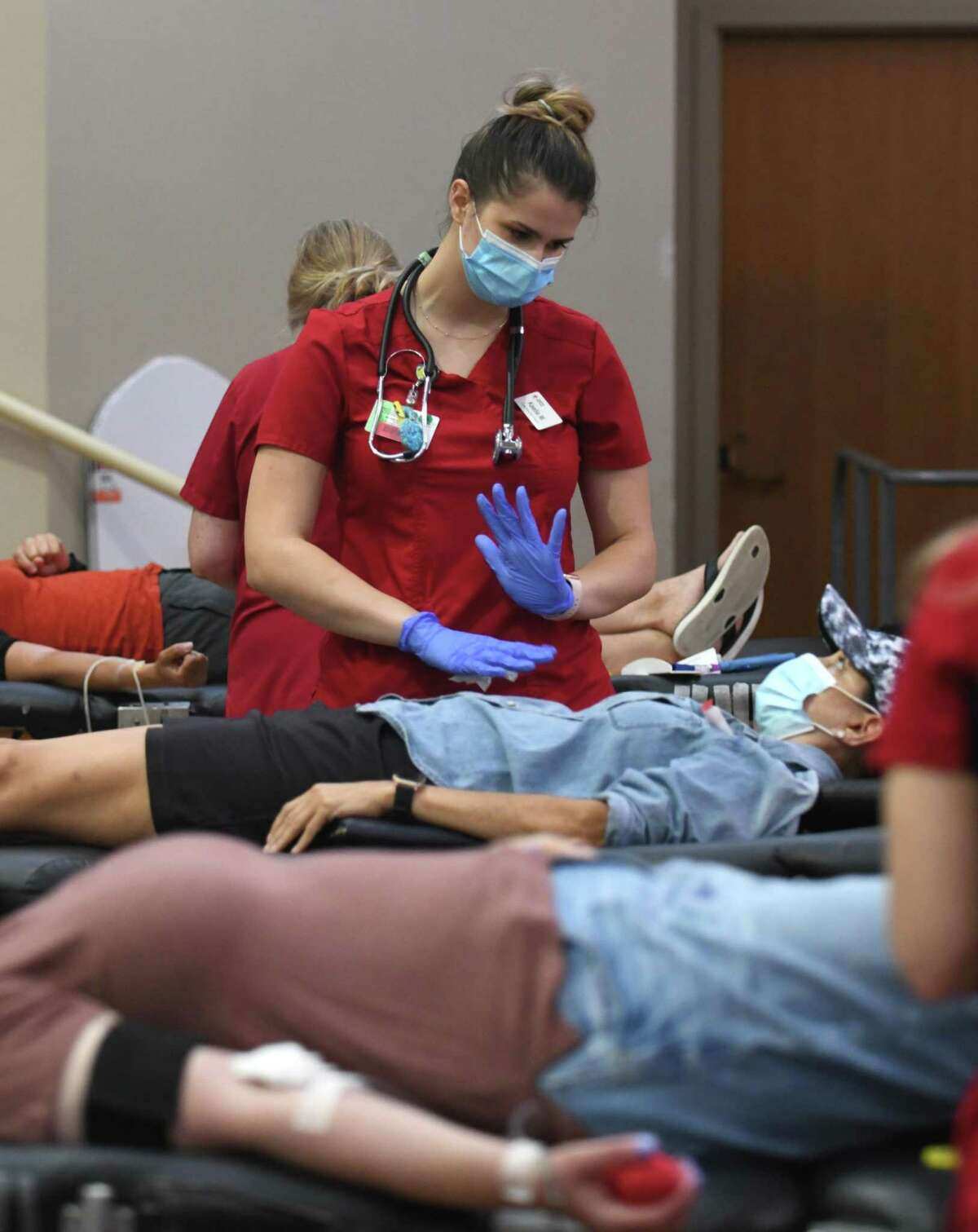 Collections technician Kaelie Murray-Simmons assists a donor during the American Red Cross blood drive at Temple Sholom in Greenwich, Conn. Monday, Aug. 2, 2021.