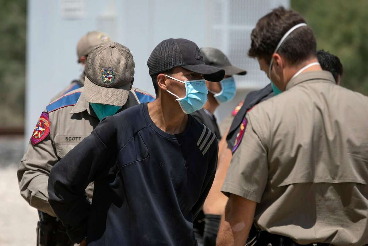 A migrant arrested at a train depot in Kinney County is loaded into a van to be booked and sent to a Texas prison on Aug. 25, 2021.